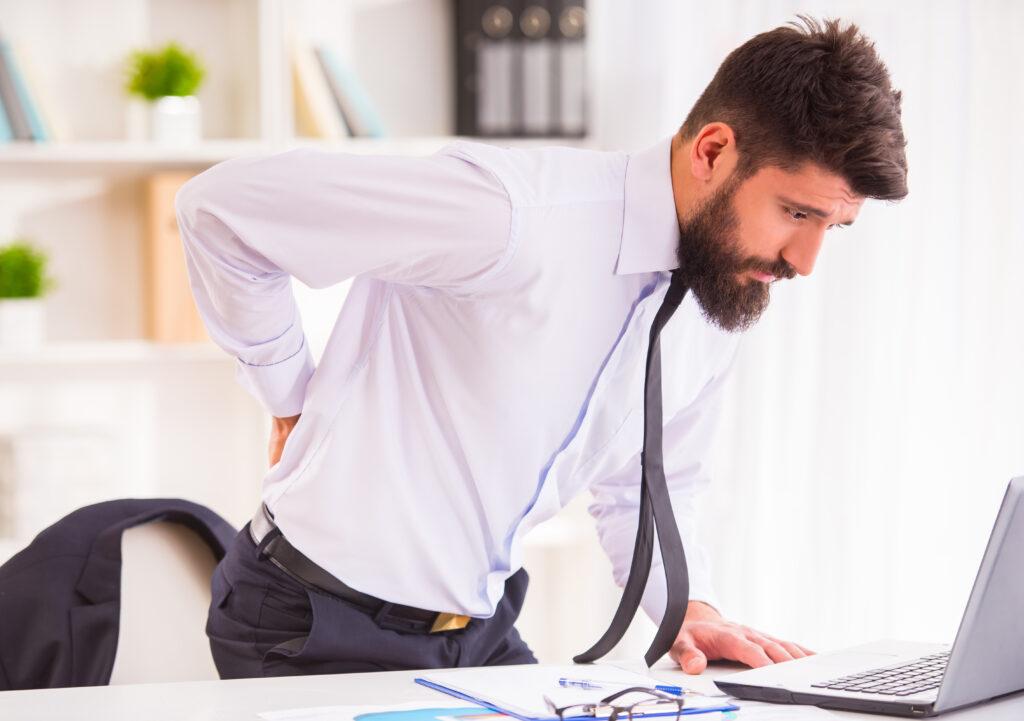 Man holding back stood over his desk - Office Insurance, Hull